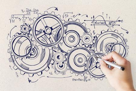 Mano che disegna schizzo creativo della ruota dentata sul fondo del muro di cemento. Concetto di dispositivo e sistema Archivio Fotografico