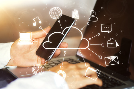 Hands using laptop and smartphone with digital interface. Technology and cloud computing concept