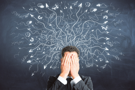 Businessman covering face on chalkboard background with drawn arrows. Risk and confusion concept  Stock Photo