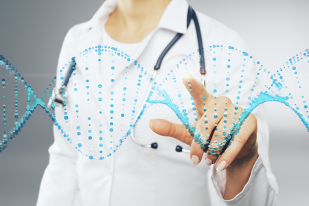 Unrecognizable female doctor pointing at abstract blue DNA. Medicine concept 写真素材 - 100849794