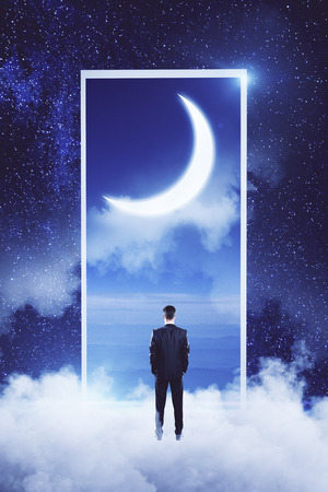 Back view of young businessman standing on abstract cloud sky background. Dream and imagination concept Stok Fotoğraf