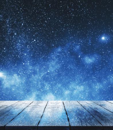 Leere Holzoberfläche auf Sternenhimmelhintergrund. Träume und Designkonzept