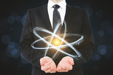 Businessman holding creative atom on blurry dark wallpaper. Medicine and science concept