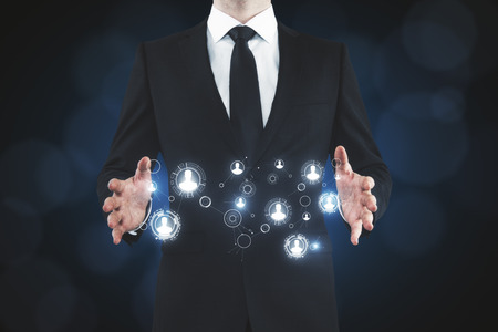 Businessman holding abstract glowing HR hologram on blurry background. Recruiting and future concept