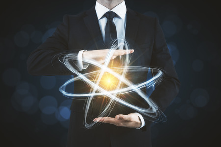 Businessman holding creative atom on blurry dark background. Medicine and science concept Stok Fotoğraf