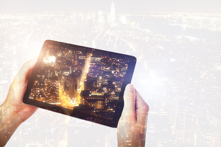 Hand taking picture of city with tablet. Photography and art concept. Double exposure