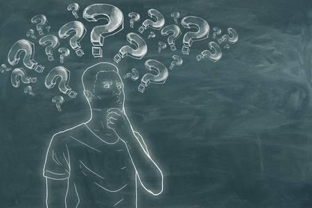 Thoughtful businessman with drawn question marks on chalkboard background. Ask and think concept
