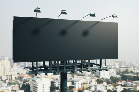 Clean black billboard on bright city background. Retail, advertisement and commerce concept. Mock up, 3D Rendering