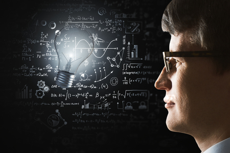 Side portrait of young businessman with illuminated lamp and mathematical formulas. Idea, science and innovation concept