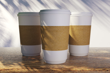 Empty coffee cups with palm tree shadows. Vacation and cafe ad concept. Mock up, 3D Rendering