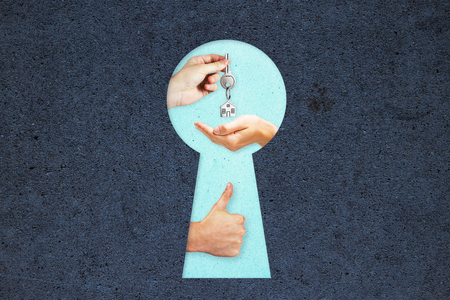 Real estate, mortgage and renting concept. Keyhole with hands on concrete background
