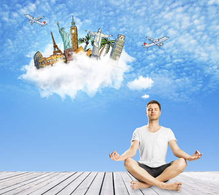 Meditating european guy thinking about travel on blue sky background. Vacation and holiday concept