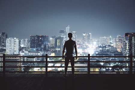 Back view of young man on rooftop looking at illuminated night city. Research and employment concept