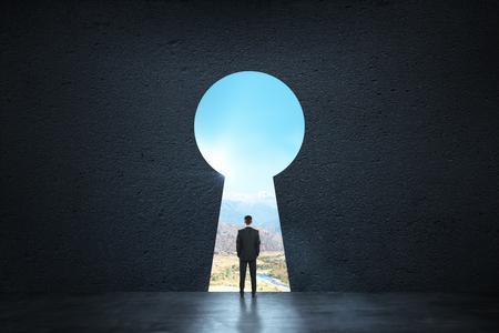 Vue arrière du jeune homme d'affaires debout contre la porte en trou de serrure. Rêve, succès, opportunité et futur concept