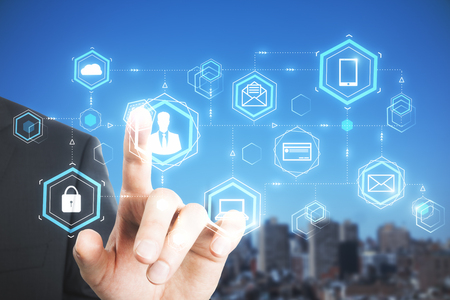 Businessman hand pointing at digital business hologram on blurry city background. Finance, blockchain and technology concept. Double exposure Stockfoto