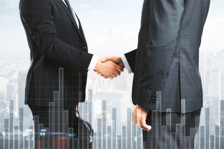 Handshake on blurry bright city background with forex chart. Analysis, finance and partnership concept. Double exposure Stockfoto