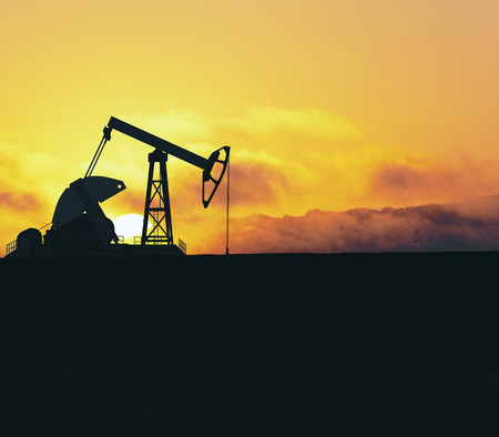 Oil pumping machine in sunlit field. Mining and quarrying concept Stock Photo