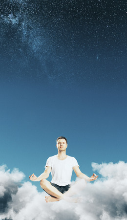 Meditating businessman in abstract starry sky with clouds. Dream and calm concept