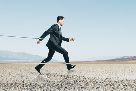 Side view of running tied businessman on desert background. Effort and success concept