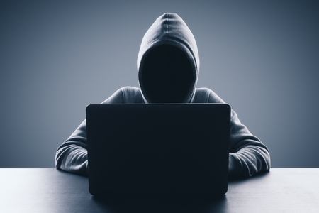 Man with hood using laptop on gray background. Hacker and virus concept. Copy space
