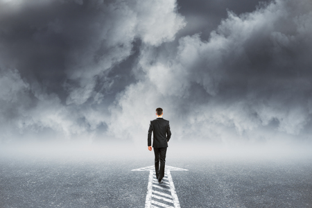 Back view of younf businessman following arrow direction on dull cloudy sky background. Choice and challenge concept 스톡 콘텐츠