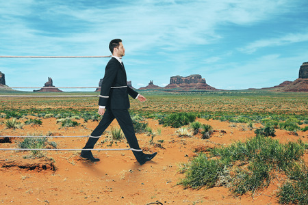 Side view of walking tied businessman on desert background. Effort and success concept Stock Photo