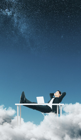 Relaxing businessman in abstract starry sky with clouds. Dream and rest concept