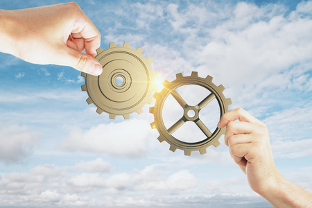 two hands of businessmen collect the gear from the gears of the details of the puzzles at cloudy sky background. 3D render Stock Photo