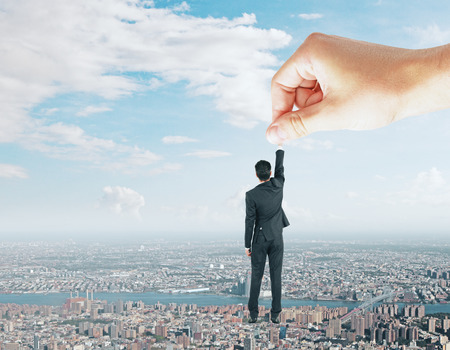 Hand holding young businessman on abstract city sky background. Manipulation and success concept