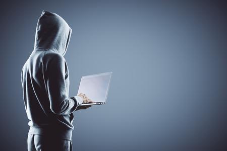 Vista lateral del pirata informático con capucha gris con portátil en fondo gris. Render 3D