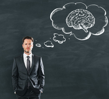 Businessman dreaming about strong brain power at school blackboard background. 3D render