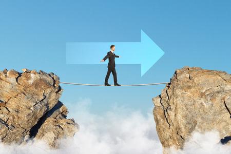 Concepto de logro objetivo con empresario caminando en la cuerda entre dos rocas en la dirección de la ciudad en el cielo azul de fondo . render 3d Foto de archivo - 104018927