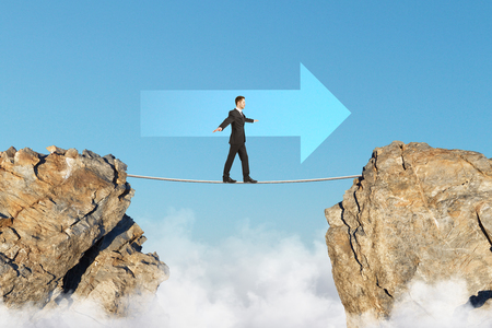 goal achievement concept with businessman walking on tightrope between two rocks in arrow direction at blue sky background. 3D render Stock Photo