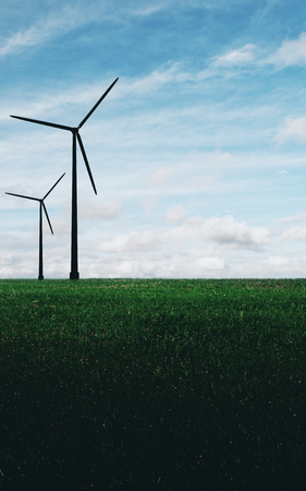 Creative backlit wind mills in fiels. Sky background. Eco concept