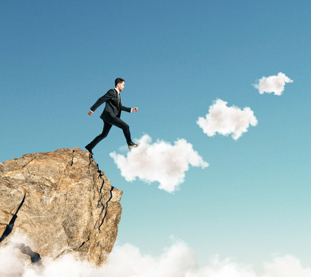 goal achievement concept with businessman climbs up the clouds at blue sky background.
