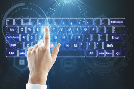 top view on businessman hand typing on virtual keyboard at abstract technology background.