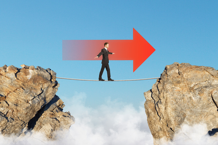 goal achievement concept with businessman walking on tightrope between two rocks in red arrow direction at blue sky background. 3D render