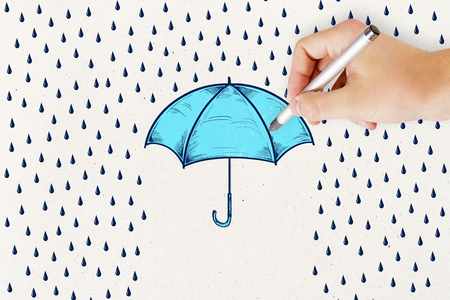 concept of protection and security wall with hand and pencil drawing rain and blue umbrella.