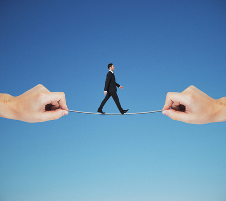 goal achievement concept with businessman walking on a tightrope between two hands at blue sky background.