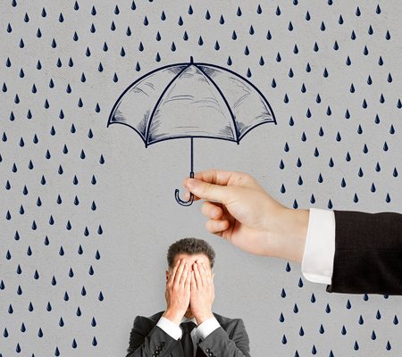 Concept of difficulty in business with umbrella and businessman closing his eyes by hands. 스톡 콘텐츠
