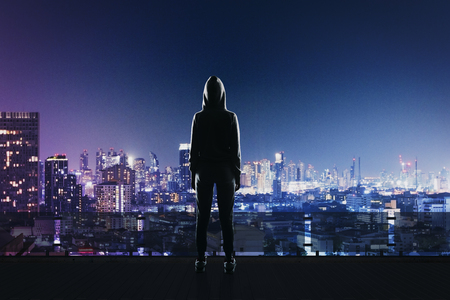 back view of hacker in sport suit standing on roof top above night megapolis city Stock Photo