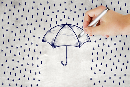 concept of protection and security wall with hand and pencil drawing rain and umbrella.