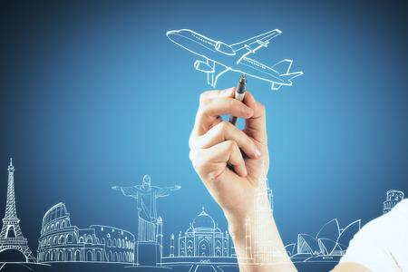 travel concept with man hand drawing airplane and world famous landmarks at blue background