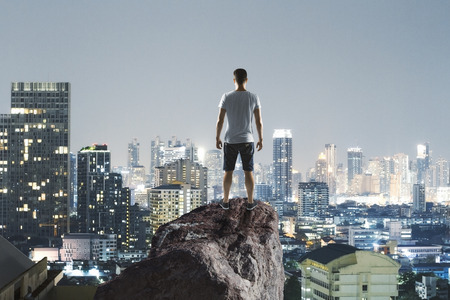 freedom concept with traveller on top of the rock with night megapolis city background