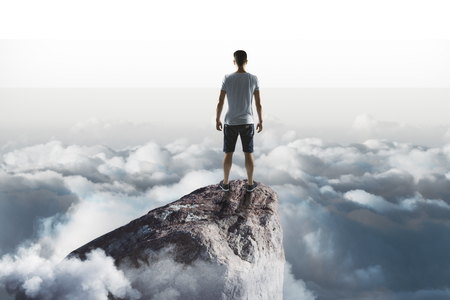 travel success concept  with traveler staring into the distance from top of the rock above the clouds.