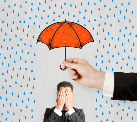 Concept of difficulty in business with hiding from rain under umbrella businessman closing his eyes by hands.