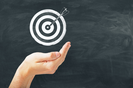 bullseye is a target of business, dart is an opportunity and dartboard is the target and goal. challenge in business marketing concept at blackboard background