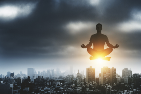 yoga time with man relaxing in lotus position in the air above dark megapolis city at stormy sky background Stock Photo