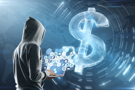 cyber attack concept with hacker in grey hoody with laptop and multimedia icons on screen. digital dollar sign background.