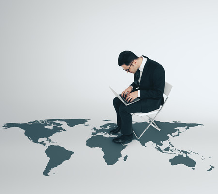 international job with businessman working on laptop, sitting on white chair and world map illustration on the floor
